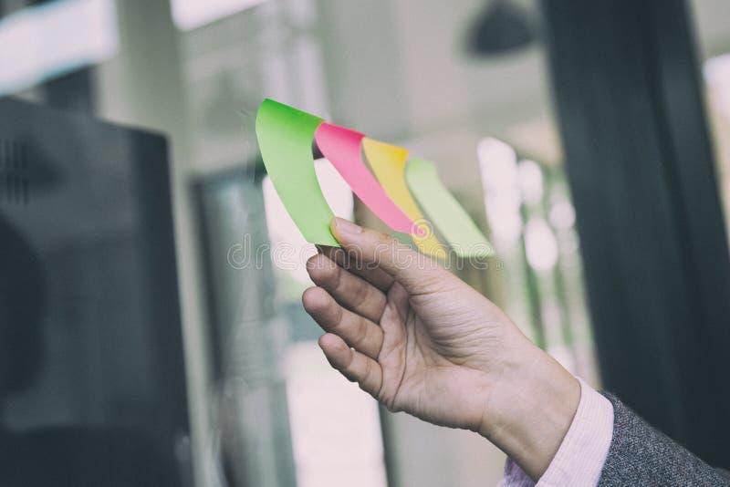 mano de la persona del negocio que lleva a cabo la nota de papel pegajosa en blanco sobre la ventana i imagen de archivo libre de regalías
