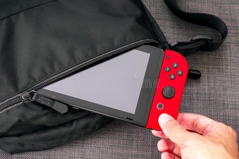 Mano de la persona que saca la consola del videojuego del interruptor de Nintendo del bolso negro fotos de archivo