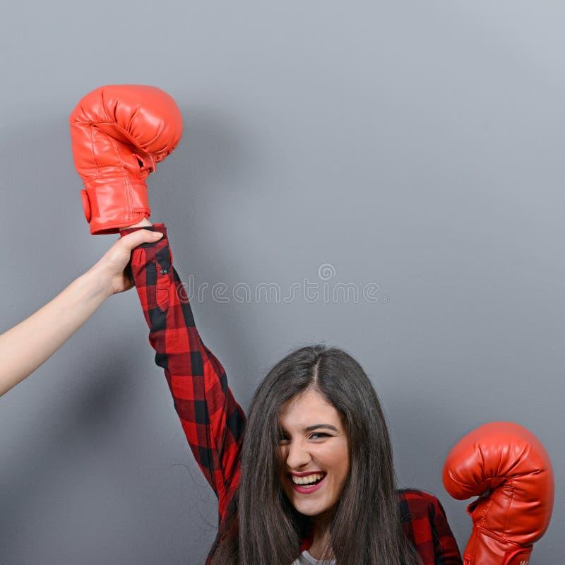 Mano de la tenencia del juez del campeón del boxeo de la mujer contra fondo gris fotografía de archivo libre de regalías