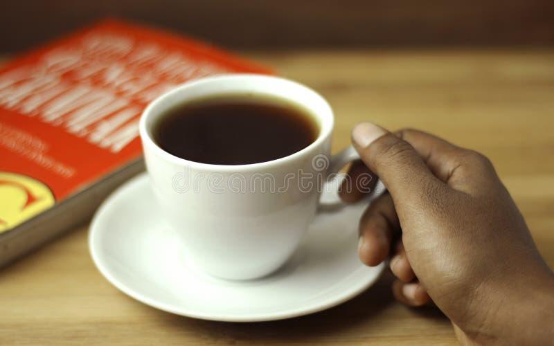 Mano de la tenencia de la taza de té con el libro rojo imagenes de archivo