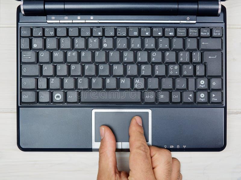 Mano de la visión superior usando el teclado del ordenador portátil del panel táctil fotografía de archivo libre de regalías
