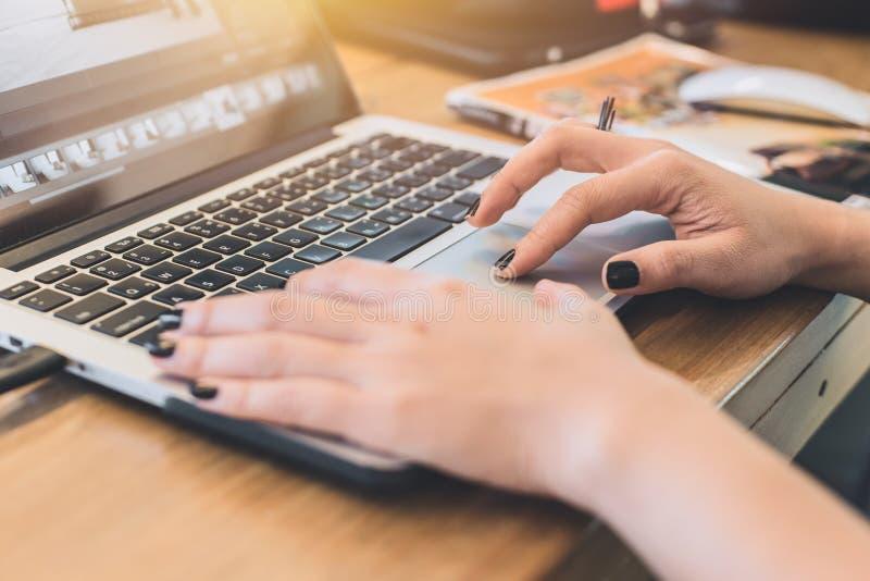Mano de las mujeres del primer usando panel táctil del ordenador portátil mientras que trabaja fotografía de archivo libre de regalías