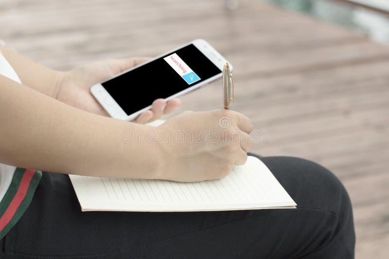 Mano de las mujeres que escriben y que miran la pantalla fotos de archivo libres de regalías