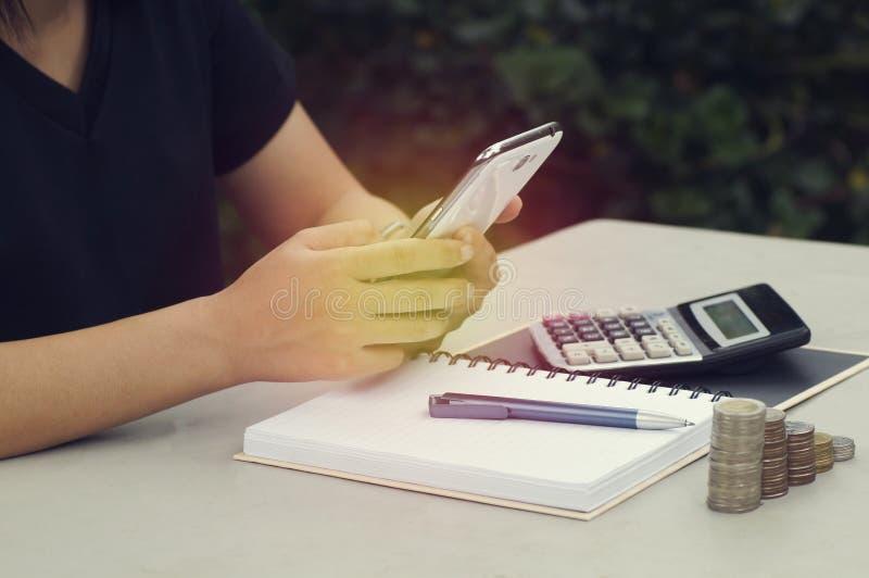 mano de las mujeres que usan smartphone con la moneda y el objeto comercial encendido fotos de archivo libres de regalías