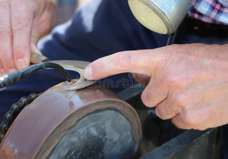 Mano de las rutinas de un viejo hombre mientras que afila su cuchilla del podón encendido imagen de archivo libre de regalías