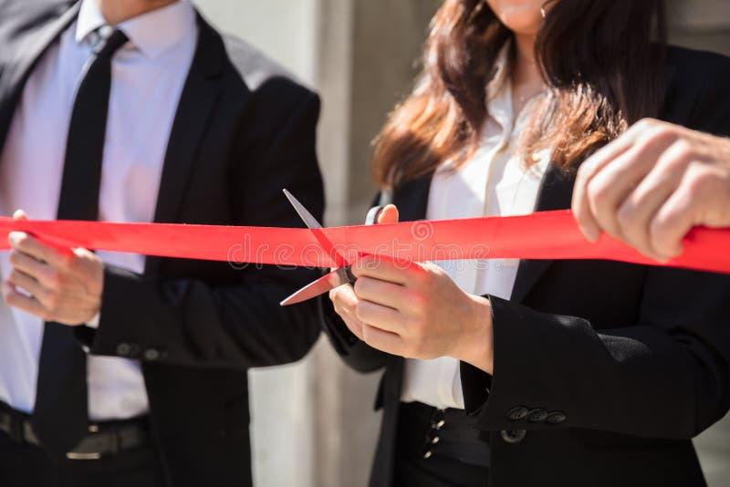 Mano de los empresarios que corta la cinta roja fotos de archivo libres de regalías