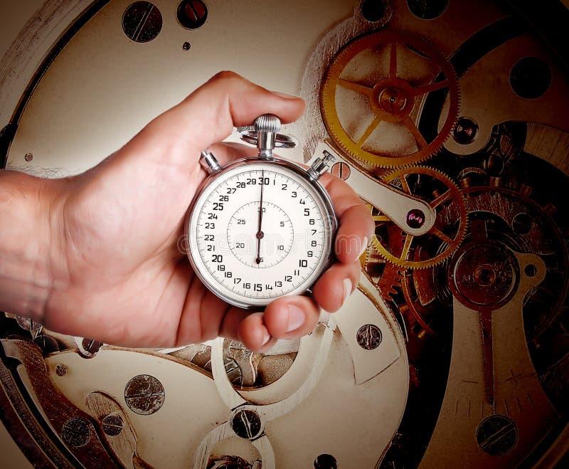 Mano de los hombres con el mecanismo del temporizador y del reloj fotos de archivo libres de regalías