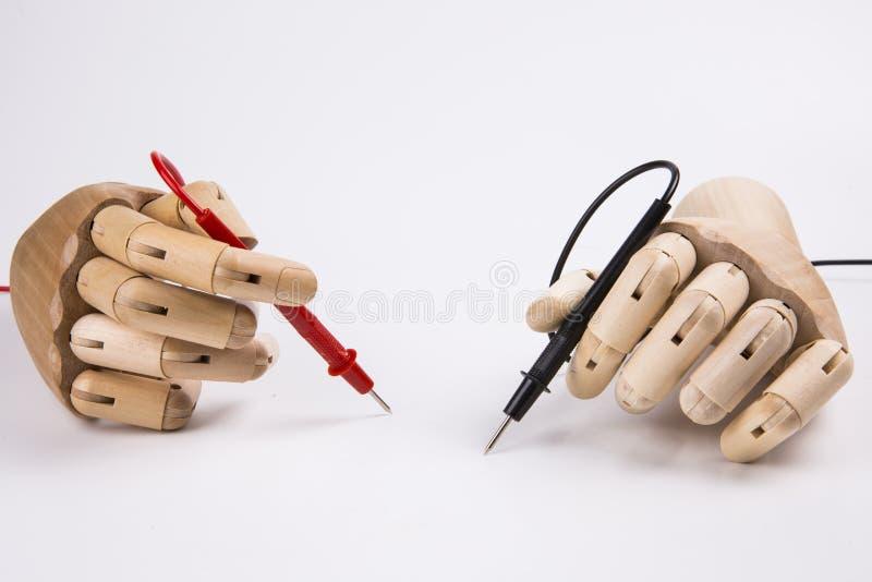 Mano de madera y multímetro eléctrico imágenes de archivo libres de regalías