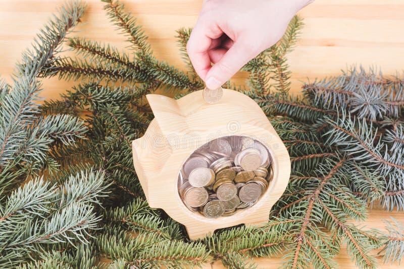 Mano de Men?s que pone la moneda de la rublo rusa en la hucha de madera Concepto del ahorro del dinero productos del taller de la imágenes de archivo libres de regalías