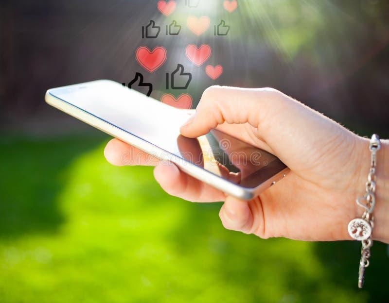 mano de mujer y x27 con smartphone al aire libre - comunicación en línea - iconos de los medios sociales imagen de archivo libre de regalías