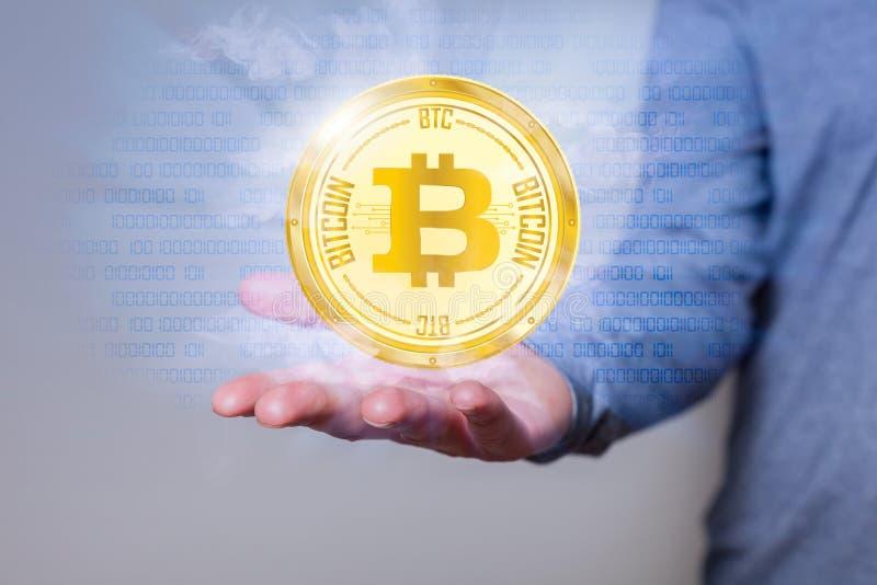 Mano de oro del ser humano de la moneda de Bitcoin fotografía de archivo