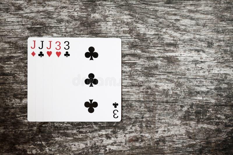 Mano de póker: casa llena extracto del juego de naipes en tabla de madera imágenes de archivo libres de regalías