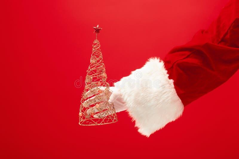 Mano de Santa Claus que sostiene un árbol de navidad del juguete en fondo rojo fotos de archivo