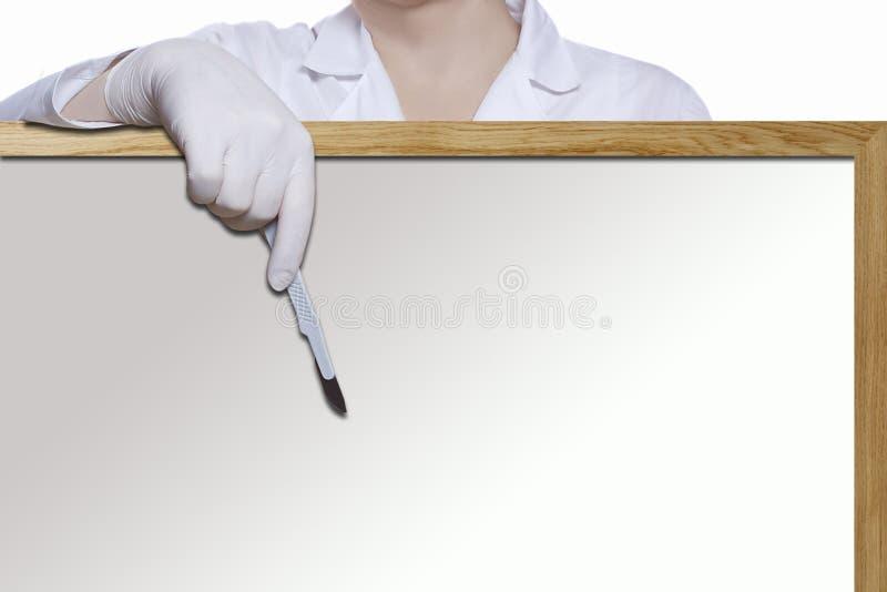 Mano de un doctor de la mujer con un escalpelo imagenes de archivo