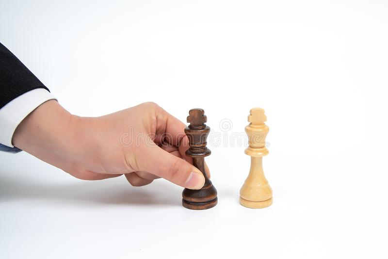 Mano de un hombre de negocios móvil que lleva a cabo un pedazo de ajedrez del rey Concepto de la negociación del negocio fotografía de archivo