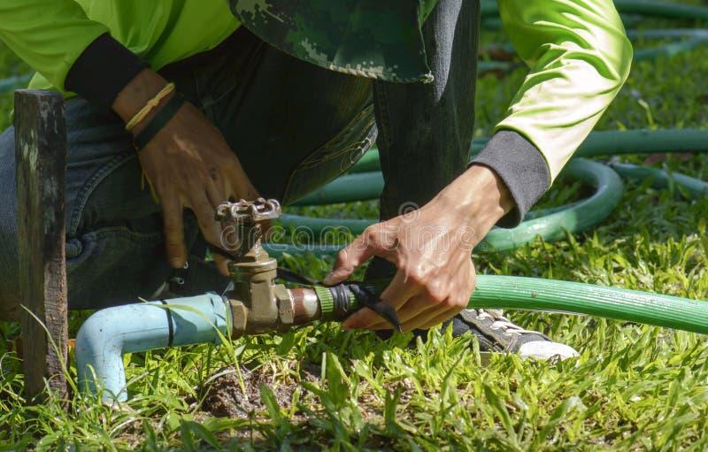 Mano de un hombre que conecta un tubo con un golpecito en jardín foto de archivo