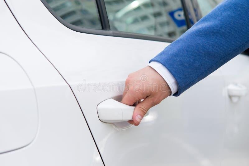 Mano de un hombre que intenta abrir la puerta de atrás de un coche blanco fotografía de archivo