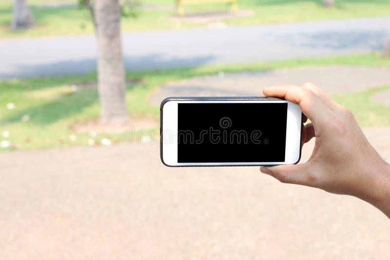 Mano de un hombre que sostiene Smartphone para el selfie en el jardín y la ha imagenes de archivo