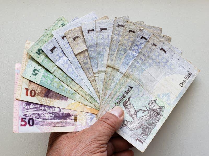 mano de un más viejo hombre que sostiene los billetes de banco de Qatar fotografía de archivo libre de regalías