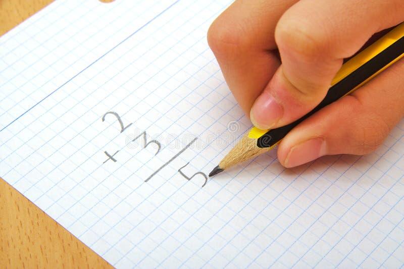 Mano de un niño que hace una suma matemáticas Concepto de la escuela fotografía de archivo