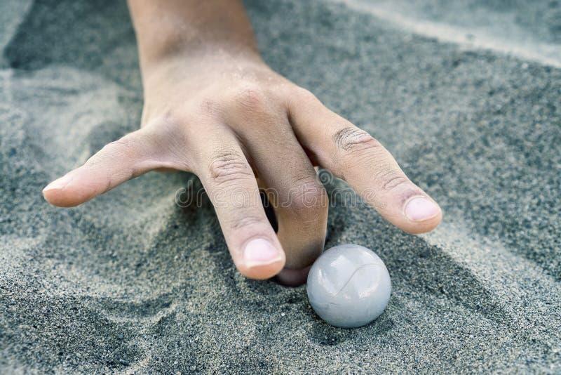 Mano de un niño que juega con mármoles fotografía de archivo