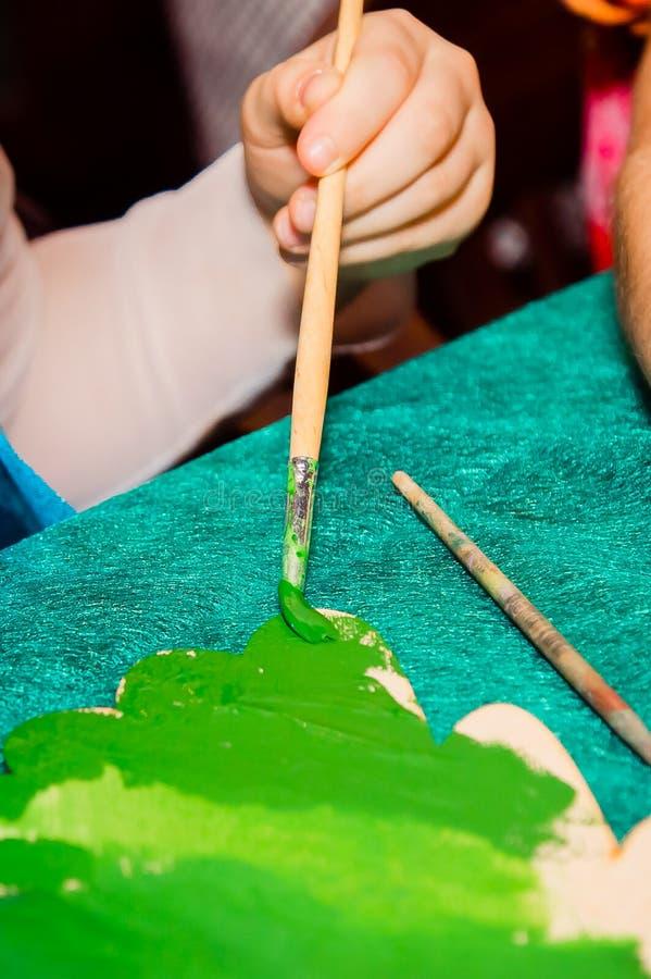 Mano de un niño que pinta un árbol de navidad con un cepillo fotografía de archivo libre de regalías