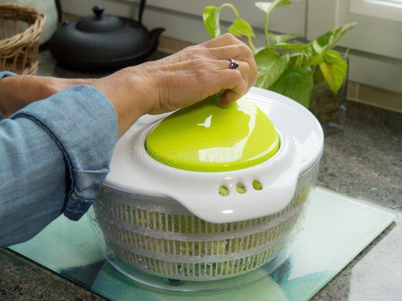 Mano de una ensalada de giro de la mujer en la cocina foto de archivo