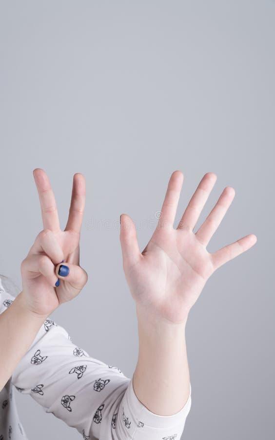 Mano de una muchacha que muestra siete fingeres foto de archivo
