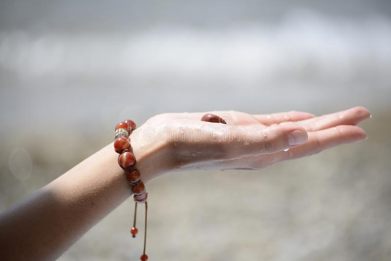 Mano de una muchacha que sostiene una piedra del mar fotos de archivo
