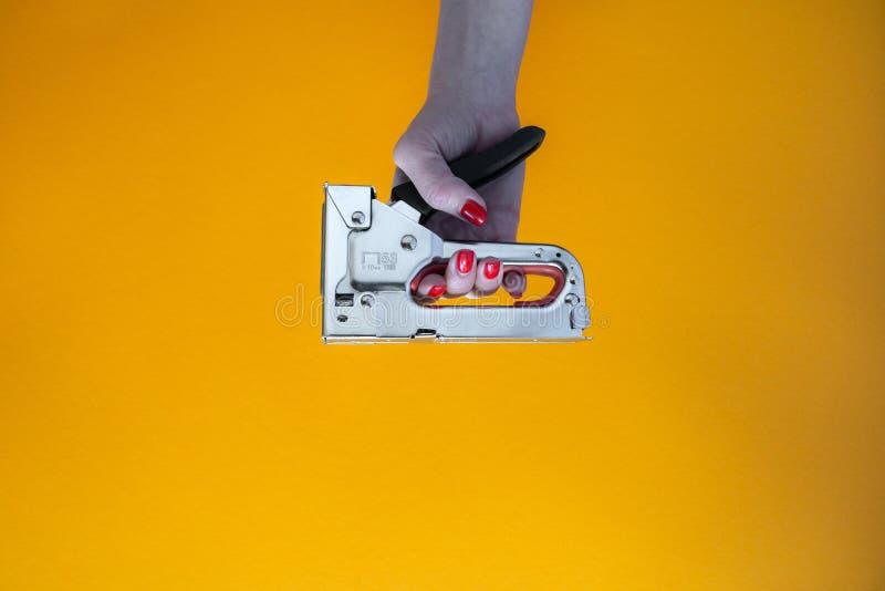 Mano de una mujer joven que sostiene una grapadora del metal fotografía de archivo