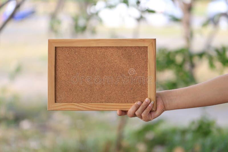 Mano de una mujer de negocios que lleva a cabo un marco de madera vacío encendido foto de archivo