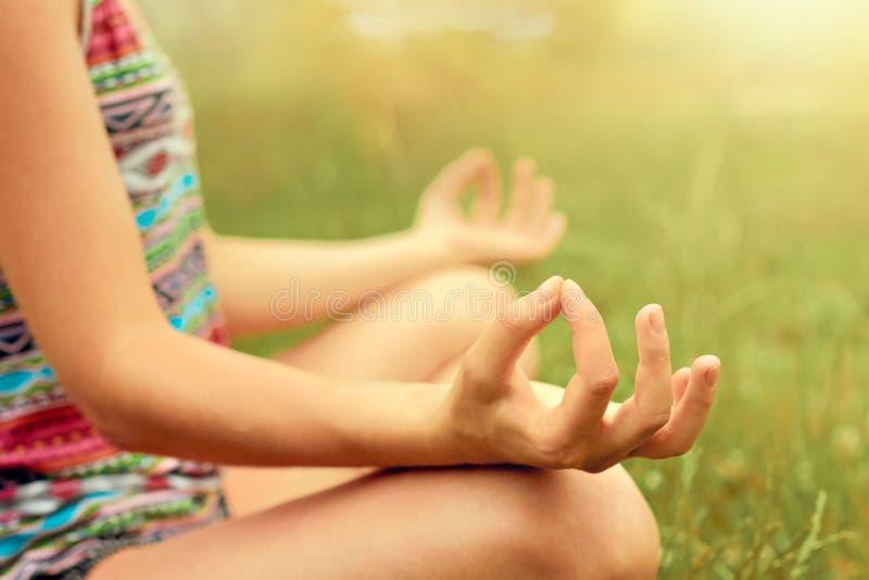 Mano de una mujer que medita en yoga practicante de la posici?n de loto en verano Forma de vida activa Concepto sano y de la yoga imagen de archivo libre de regalías