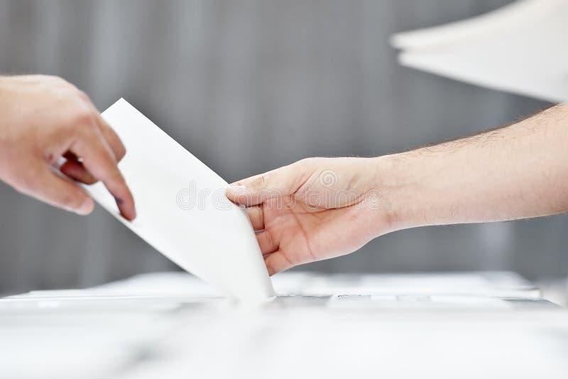 Mano de una persona que emite un voto foto de archivo libre de regalías