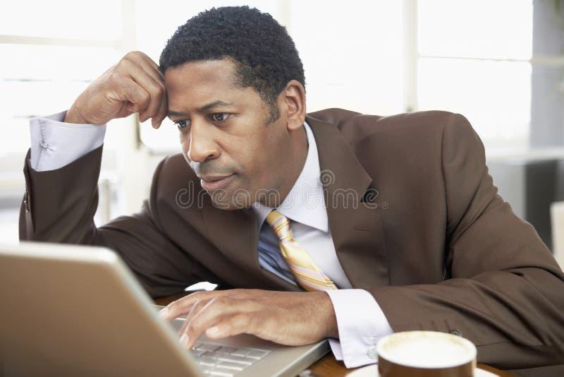 Mano de Using Laptop With del hombre de negocios en la cabeza fotos de archivo