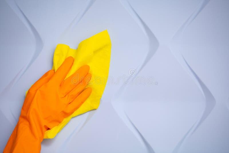 Mano degli impiegati in guanto protettivo di gomma arancio che pulisce parete blu 3d da polvere con lo straccio asciutto giallo P immagini stock