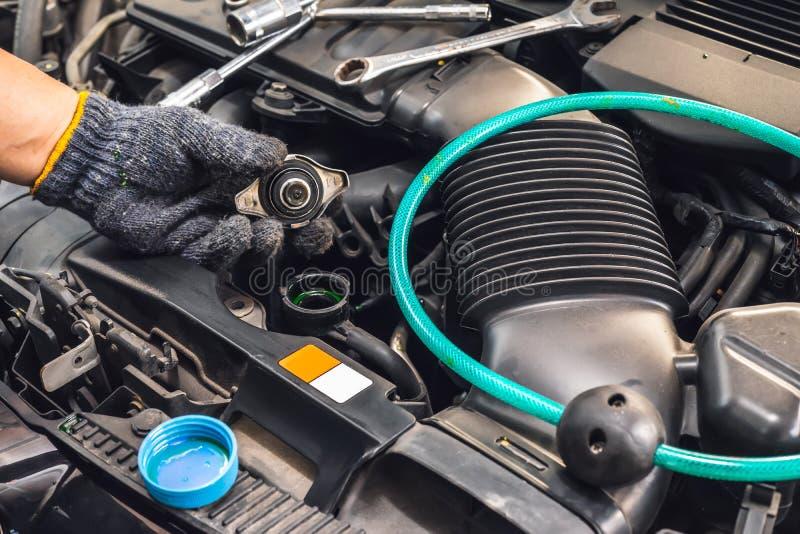 Mano del agua del control del mecánico en radiador del coche y añadir el líquido del líquido refrigerador del anticongelante del  foto de archivo