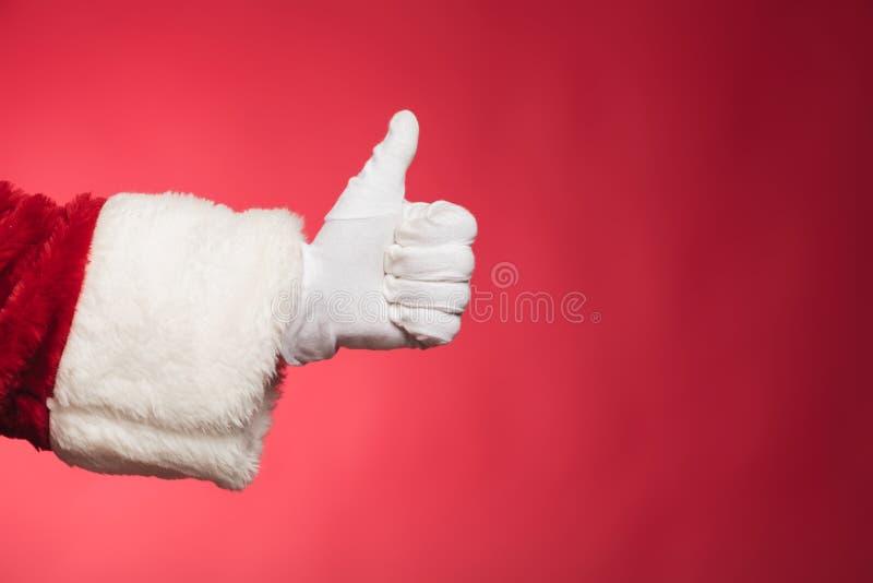 Mano del Babbo Natale che mostra i pollici sul segno giusto fotografia stock