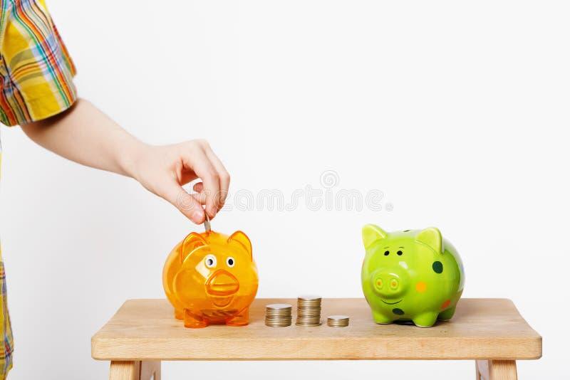 Mano del bambino che mette moneta in un porcellino salvadanaio fotografia stock libera da diritti
