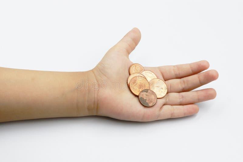 Mano del bambino che mostra le monete dei soldi, bambino tenendo le monete sul suo isolato della mano sul backgroundo bianco immagini stock
