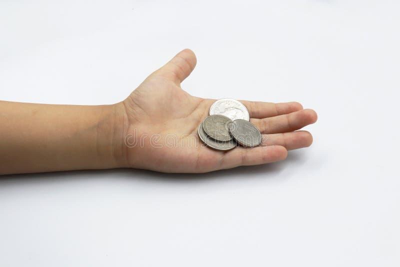Mano del bambino che mostra le monete dei soldi, bambino tenendo le monete sul suo isolato della mano su fondo bianco fotografia stock libera da diritti