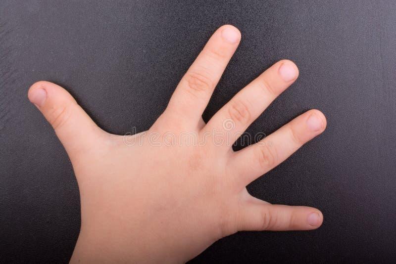 Mano del bambino con fondo scuro fotografie stock