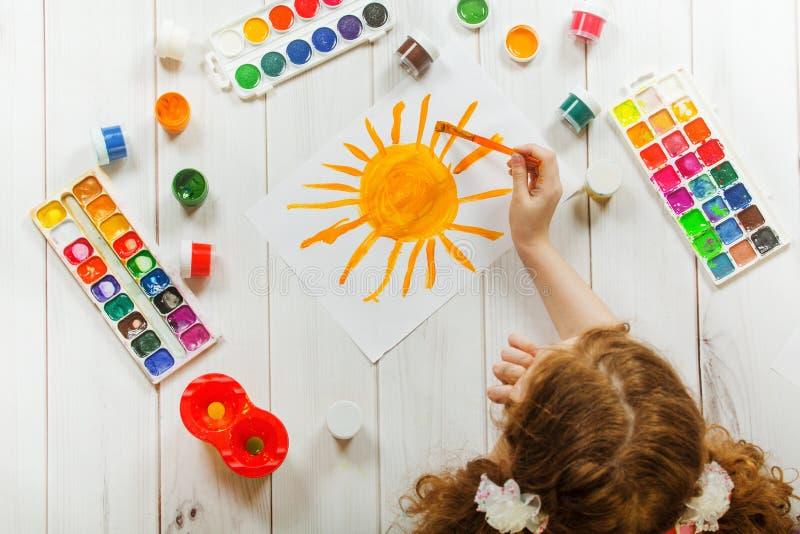 Mano del bambino con le spazzole che attingono il sole di giallo del Libro Bianco fotografie stock