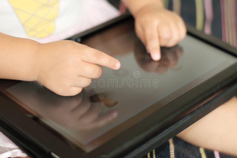 Mano del bambino facendo uso del primo piano del PC della compressa dello schermo attivabile al tatto immagine stock
