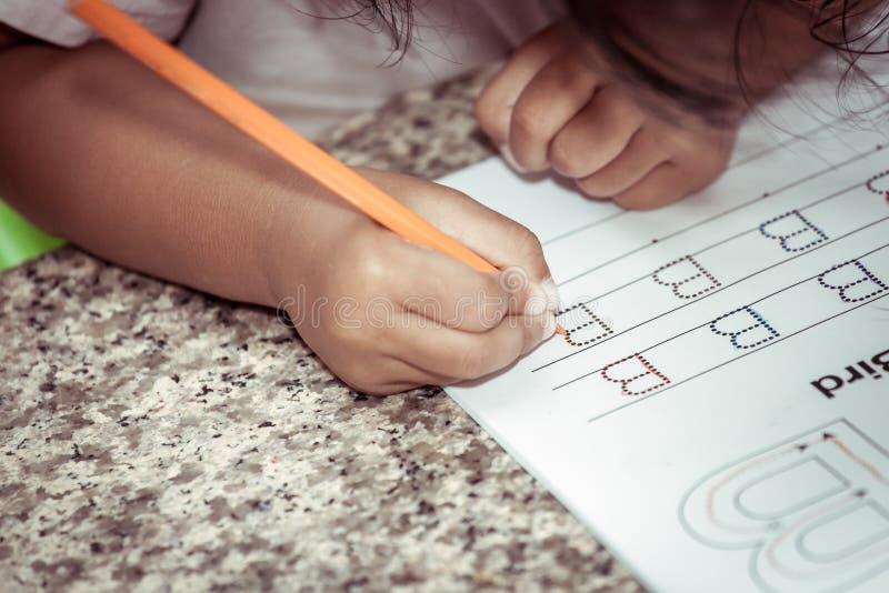 Mano del bambino le che scrive compito con il pastello fotografia stock libera da diritti