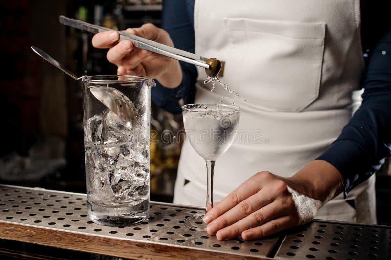 Mano del barista che mette un'oliva in un vetro di cocktail fotografie stock libere da diritti