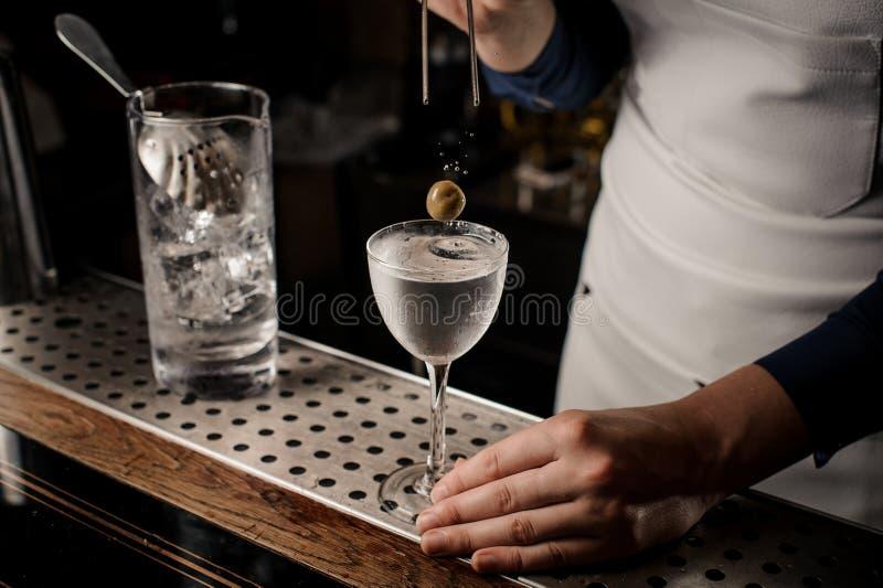 Mano del barista che mette un'oliva in un vetro di cocktail elegante fotografia stock libera da diritti