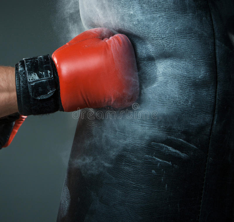Mano del boxeador y del saco de arena sobre negro fotografía de archivo libre de regalías