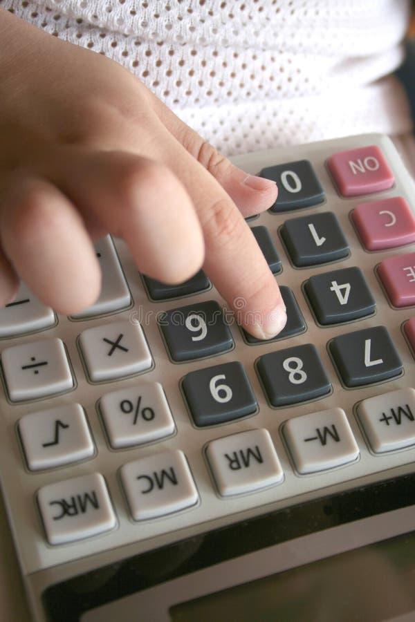 Mano del cabrito usando la calculadora fotografía de archivo