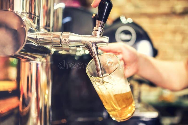 Mano del camarero en el golpecito de la cerveza que vierte una porción de la cerveza de cerveza dorada del proyecto en un restaur imagen de archivo