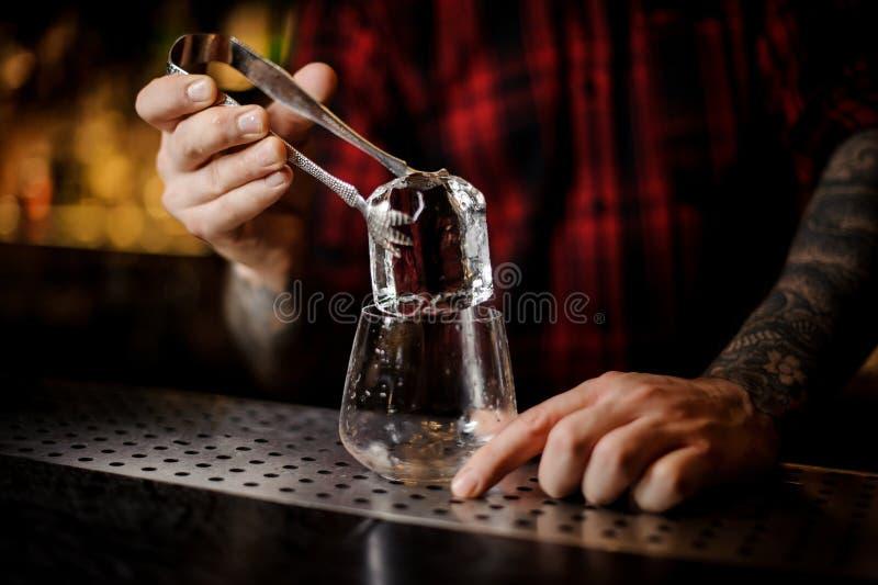 Mano del camarero que pone un cubo de hielo grande en un whisky dof fotos de archivo libres de regalías